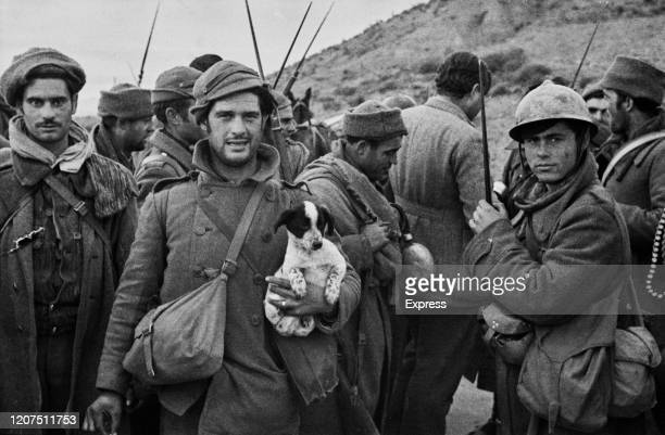 Writer and journalist Ernest Hemingway talks with Republican soldiers before they go into action on the Aragon front during the Spanish Civil War at...