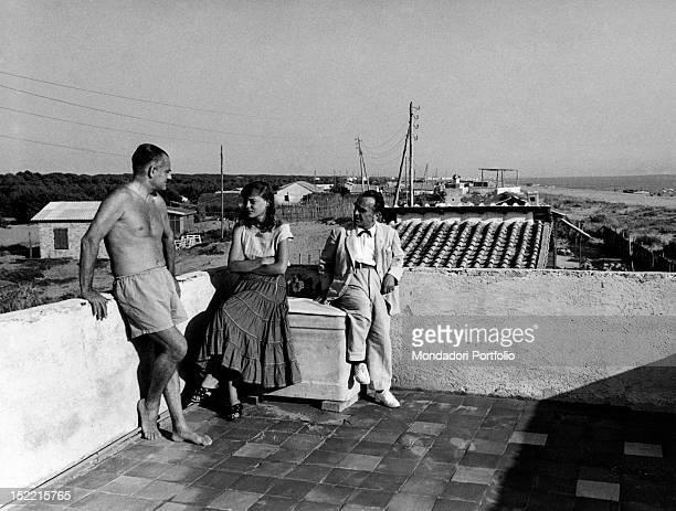 Writer and painter Amerigo Bartoli talks with Alberto Moravia in trunks and Carolina Freud on the terrace of a house near the beach Fregene September...