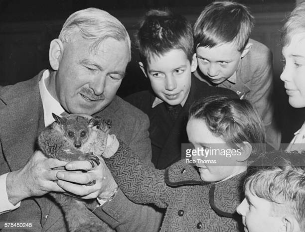 Writer and zoologist George Cansdale Superintendent of the Zoological Society of London showing a bush baby to a group of children as little Margaret...