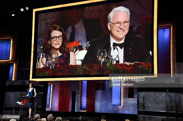 Writer Anne Stringfield and honoree Steve Martin appear on a video screen above writer/actress Tina Fey speaking onstage during the 43rd AFI Life...