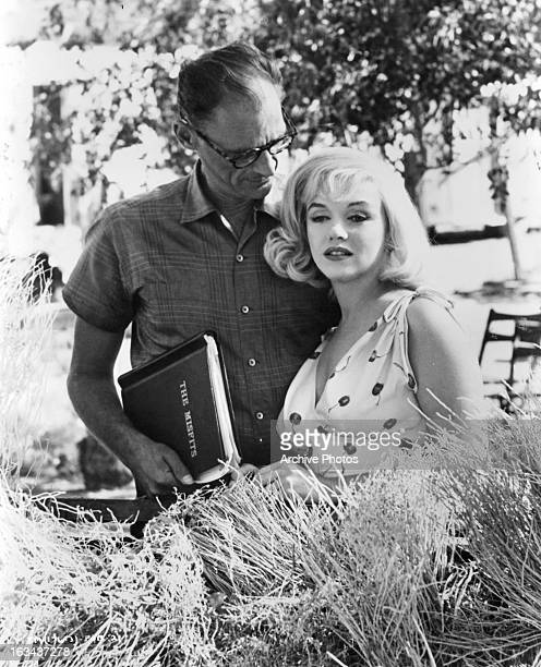 Writer Arthur Miller standing over Marilyn Monroe in between scenes from the film 'The Misfits' 1961