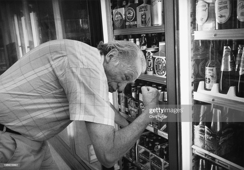 Writer Charles Bukowski flexes his muscles as he removes a six-pack of beer from a store cooler, 1996.