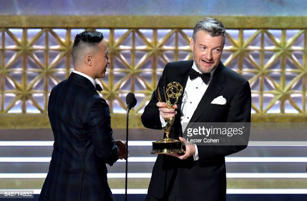 Writer Charlie Brooker accepts the Outstanding Television Movie award for 'Black Mirror San Junipero onstage from actor BD Wong during the 69th...