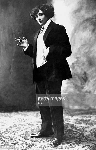 Writer Colette wearing man 's suit and smoking , photographed by Henri Manuel, c. 1906-1909