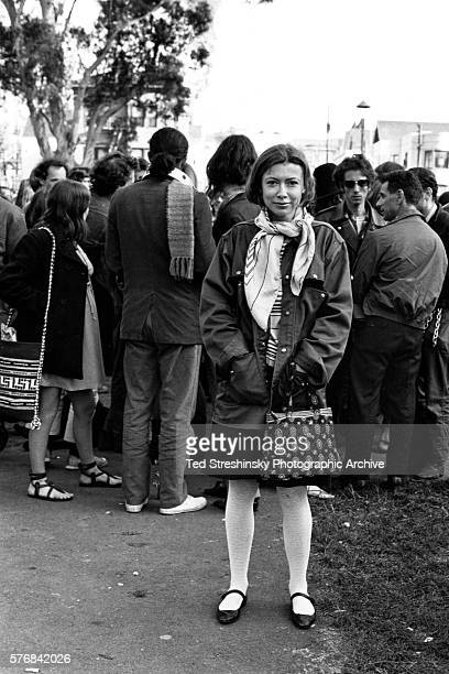 Writer Joan Didion stands at the panhandle of Golden Gate Park with a group of hippies during the writing of her article Slouching Towards Bethlehem...