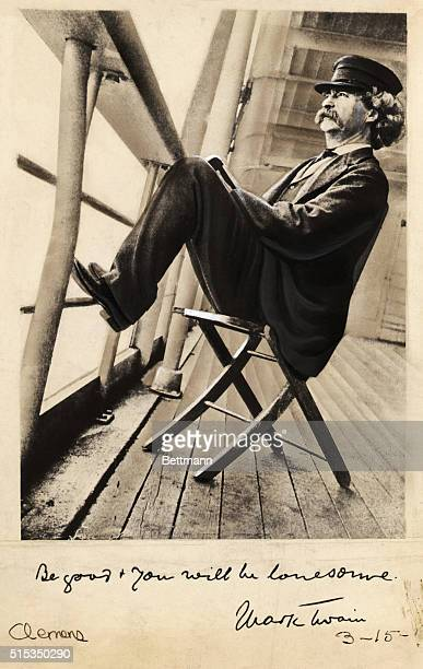 Writer Mark Twain relaxes on a ship deck with his feet on the railings