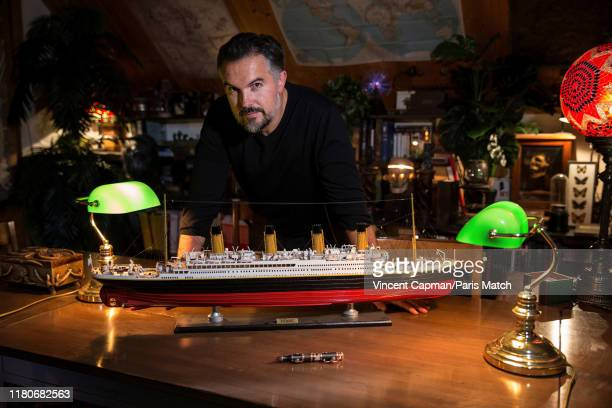 Writer Maxime Chattam is photographed with a model of the Titanic ocean liner and a pen made with pieces from the actual ship in his office for Paris...