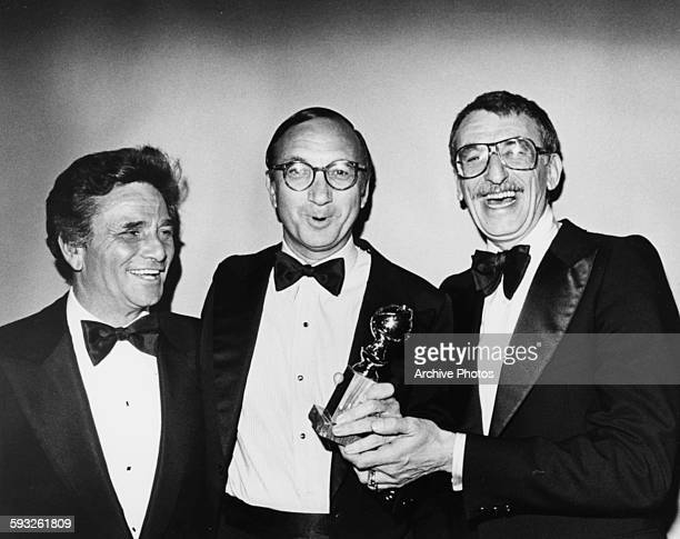 Writer Neil Simon holding his Best Screenplay Award with actor Peter Falk and director Herbert Ross at the Golden Globe Awards January 1978