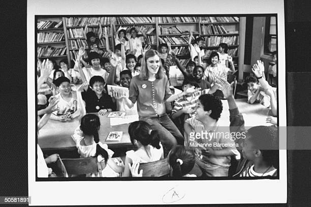 Writer of preteen novels The BabySitters Club series Ann Martin sitting on desk surrounded by her adoring young fans at her official fan club at PS 2...