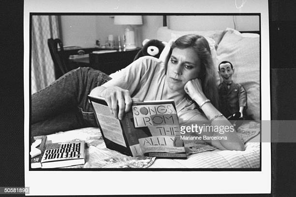 Writer of preteen novels The BabySitters Club series Ann Martin reading Songs From the Alley by Kathleen Hirsch while lying on bed next to Pee Wee...