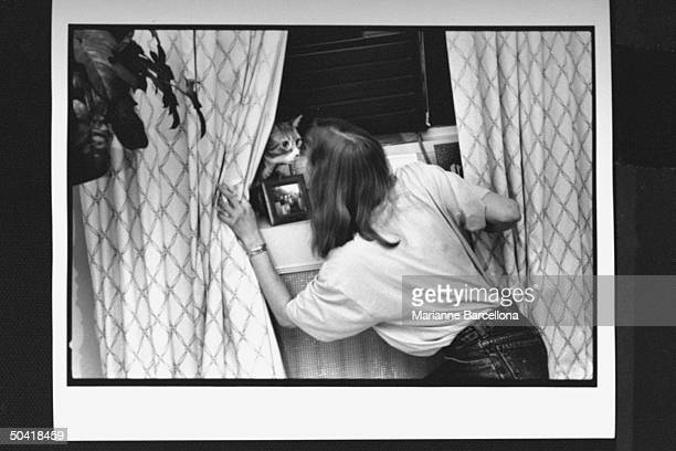 Writer of preteen novels The BabySitters Club series Ann Martin playing w cat Mouse hiding behind curtain at home Greenwich Village