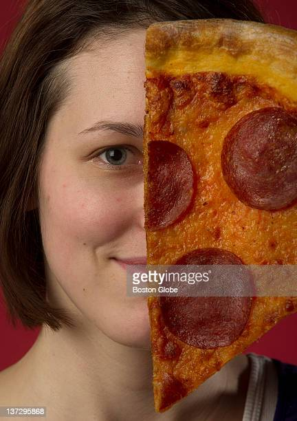 Writer poses with a slice of pepperoni pizza for a story on vegans who have turned carnivorous She is photographed at The Boston Globe's studio on...