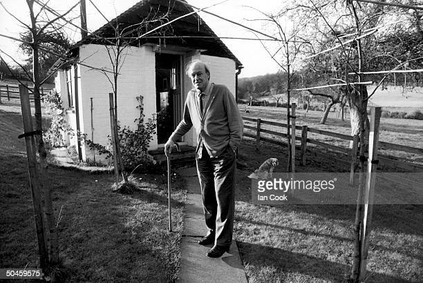 Writer Roald Dahl holds onto his cane while standing outside the shed where he writes Great Missenden Buckinghamshire England