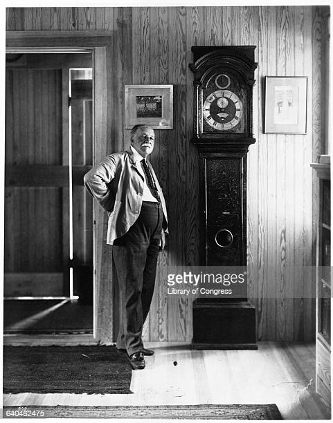 Writer William Dean Howells standing by a grandfather clock