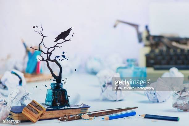 Writer workplace with raven silhouette made from splashes of ink. Typewriter, notes, pencils and papers on a light background with copy space. Creative writing concept. Dynamic shot with frozen motion.