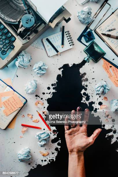 writer workplace with spilled ink, crumpled paper, scattered letters, stationery and a typewriter. ink leaving stains on an open palm. space for creative lettering. - authors stockfoto's en -beelden