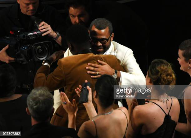 Writer/director Jordan Peele embraces actor Daniel Kaluuya before accepting Best Original Screenplay for 'Get Out' onstage during the 90th Annual...