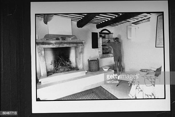 Writer/English expatriate Peter Mayle arranging books on small cutout book shelves in wall next to a large fireplace w a raised hearth at home