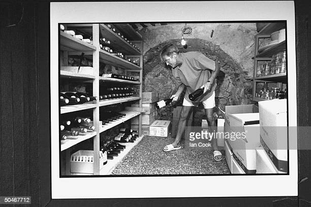 Writer/English expatriate Peter Mayle holding two bottles of wine as he prepares to put them on the shelves in his wine cellar at home