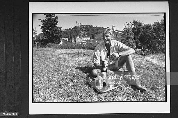 Writer/English expatriate Peter Mayle sitting on grass next to a tray that holds two bottles of wine an ice bucket as he savors a glass of wine in...