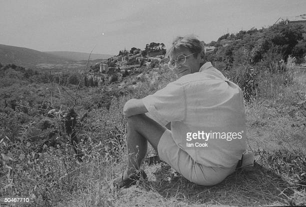 Writer/English expatriate Peter Mayle sitting on the ground w the buildings of the village on hill in the bkgrd nr his home