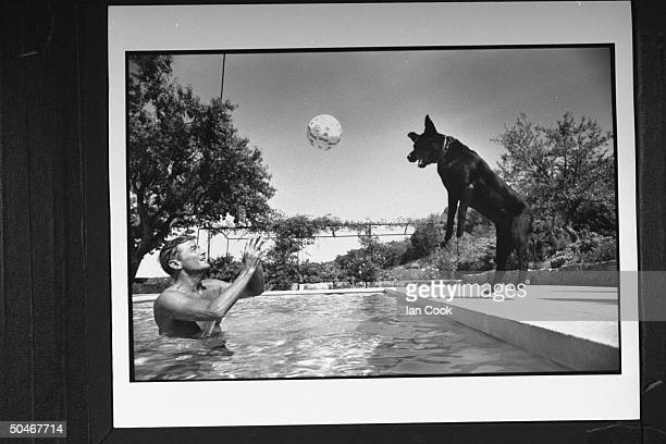 Writer/English expatriate Peter Mayle standing in swimming pool throwing ball to his dog that is leaping from the edge to catch it in midair at home