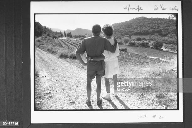 Writer/English expatriate Peter Mayle w his arm around his wife Jennie as they overlook vineyard nr their home