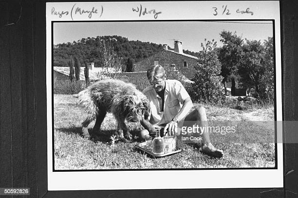 Writer/English expatriate Peter Mayle w his shaggy dog sitting on the grass as he prepares to pour a glass of wine for himself from a tray containing...