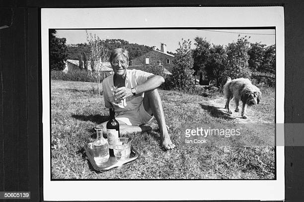 Writer/English expatriate Peter Mayle w his shaggy dog sitting on the grass as he holds a glass of wine from a tray containing 2 bottles an ice...