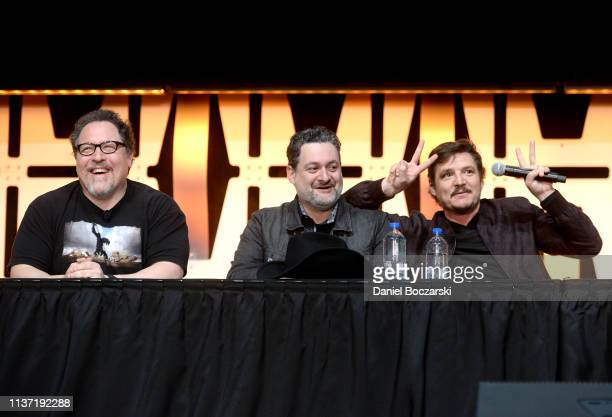 Writer/executive producer Jon Favreau Director/executive producer Dave Filoni and Pedro Pascal onstage during The Mandalorian panel at the Star Wars...