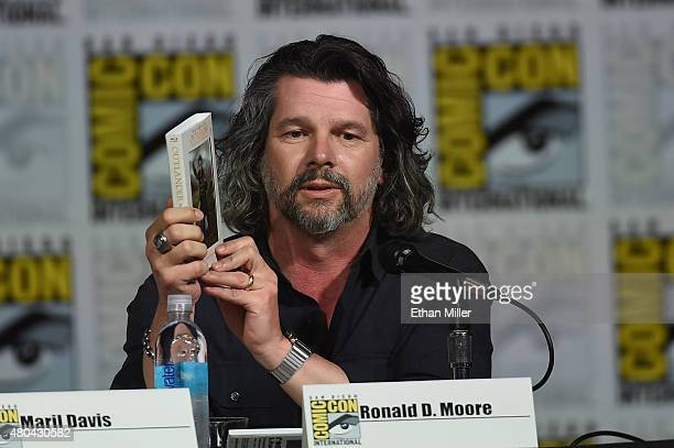 """Writer/producer Ronald D. Moore holds up an """"Outlander"""" collector's edition Blu-ray as he attends the Starz: """"Outlander"""" panel during Comic-Con..."""