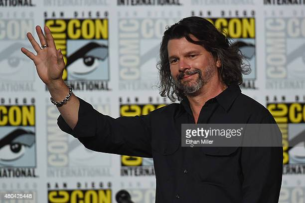 """Writer/producer Ronald D. Moore waves as he arrives at the Starz: """"Outlander"""" panel during Comic-Con International 2015 at the San Diego Convention..."""