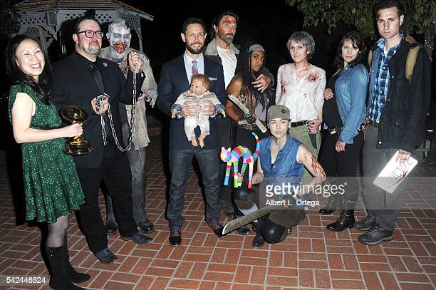 Writers Angela Kang Matt Negrete and Carey Reed of 'The Walking Dead' pose with Reel Guise TWD cosplayers at the 42nd Annual Saturn Awards After...