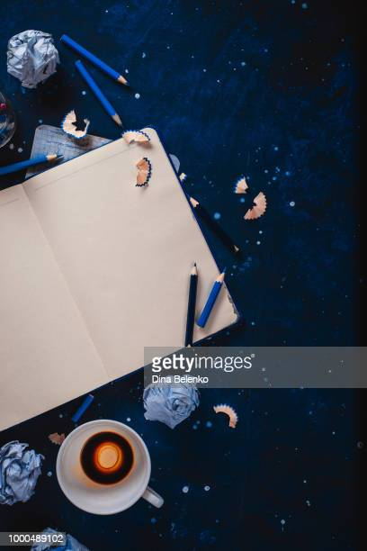 writers block concept with open notepad, empty coffee cups, pencils and crumpled paper balls on a... - the_writer's_block stock pictures, royalty-free photos & images
