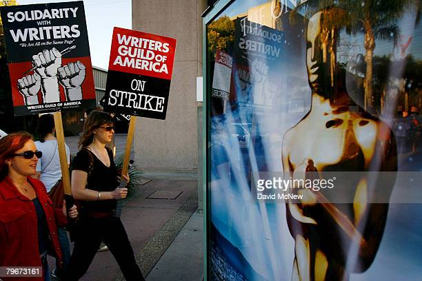 Writers Guild of America members and supporters pass a bus stop ad for the Oscars awards show while picketing in front of NBC studios as hope grows...