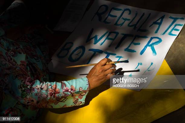 A writes on a placard prior to take part in a protest against the way the Cape Town city council has dealt with issues around water shortages on...