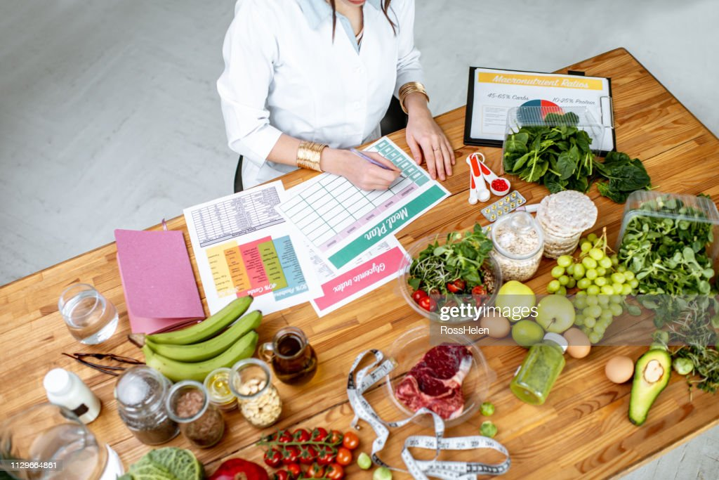 Writing a diet plan on the table full of healthy food : Stock Photo
