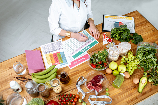Writing a diet plan on the table full of healthy food 1129664861