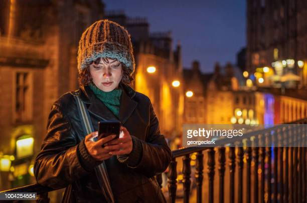 writing a smart phone message alone in the city at dusk - edinburgh scotland stock pictures, royalty-free photos & images