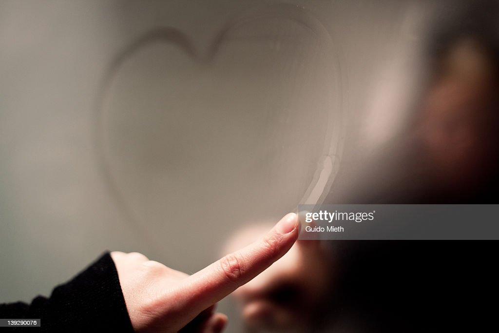 Writing heart on steamy mirror : Stock Photo