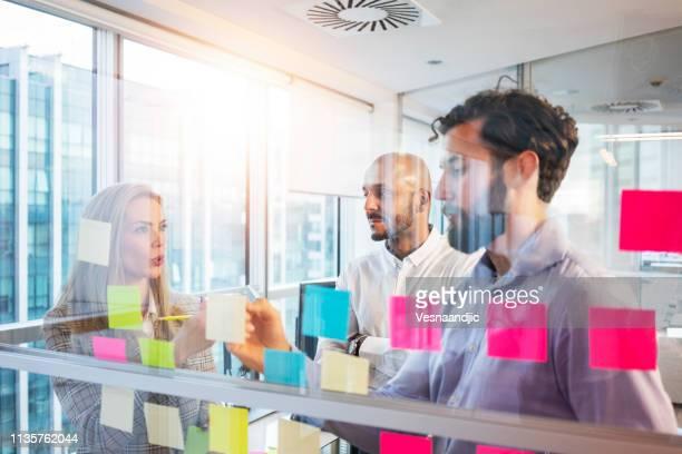 het schrijven van ideeën over sticker notes - workshop stockfoto's en -beelden
