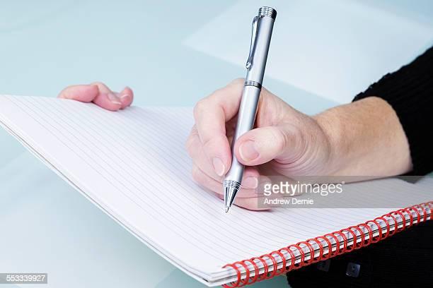 writing in a notebook - andrew dernie stockfoto's en -beelden