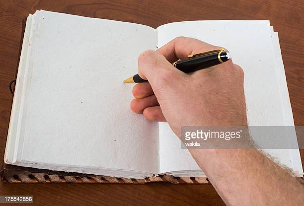 writing in empty leatherbook diary or guestbook with Ballpoint pen