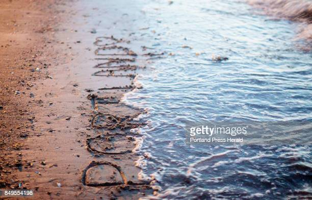 Writing in the sand said Portland 2017 is washed away by the waves at the beach next to Spring Point Ledge Lighthouse