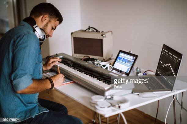 writing lyrics for song he just made - electric piano stock photos and pictures