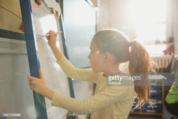 writing on the whiteboard in her elementary class - learn english stock pictures, royalty-free photos & images