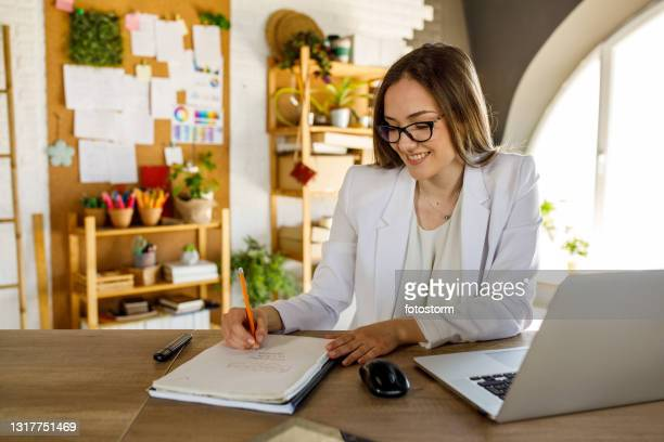 writing out a business strategy while working at her desk - list stock pictures, royalty-free photos & images