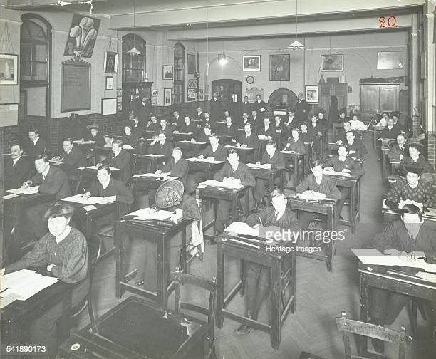 Written examination in cvc class for male and female students Queen's Road Evening Institute London 1908 Seated in a hall in long rows with teachers...