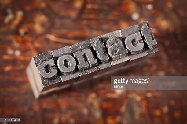 Contacter écrit en métal sur fond en bois de la typographie