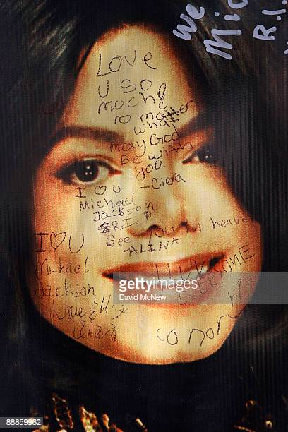 Written messages of remembrance are written on a poster at a makeshift memorial outside the Jackson family home as Los Angeles prepares for memorial...